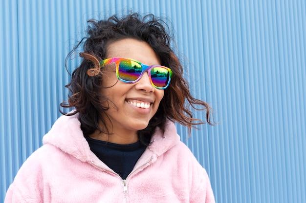 Bliska portret nastoletniej brunetki na niebieskim tle. jest uśmiechnięta i szczęśliwa, nosi okulary przeciwsłoneczne w kolorach flagi lgbt. miejsce na tekst.