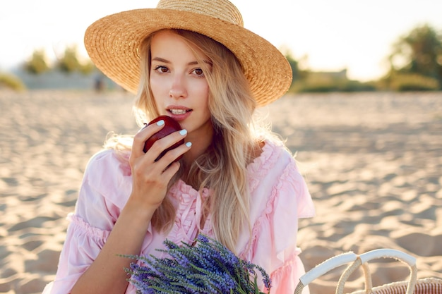 Bliska portret naturalnej białej dziewczyny w słomkowym kapeluszu korzystających z weekendów w pobliżu oceanu. pozowanie z owocami. bukiet lawendowy w torebce ze słomy.