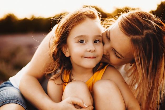 Bliska portret niesamowitej dziewczynki patrząc na kamery, uśmiechając się, będąc emraced i kised przez matkę przed zachodem słońca.