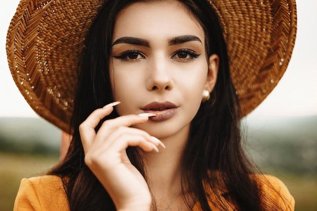Bliska portret niesamowitej kobiety o długich ciemnych włosach w kapeluszu i patrząc na aparat poważnie, dotykając jej ust palcami.