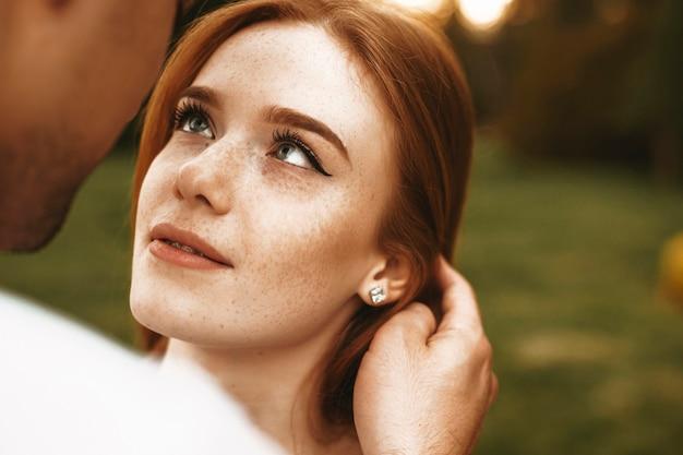 Bliska portret niesamowitej kobiety z rudymi włosami z piegami i szarymi oczami, patrząc na swojego chłopaka uśmiechniętego, gdy dotyka jej włosów na zewnątrz podczas randki.