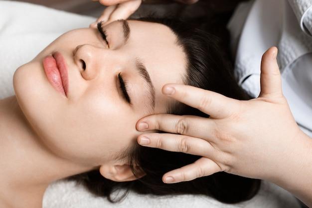 Bliska portret niesamowitej młodej kobiety siedzącej w salonie spa robi masaż twarzy przed wykonaniem maski na twarz.