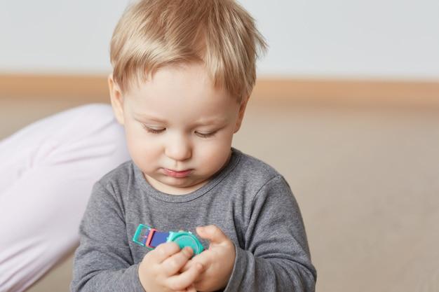Bliska portret niewinnego dzieciaka, uważnie patrząc na kolorowe dziecięce zegarki na rękę w domu. mały chłopiec w szarej koszuli z blond włosami. niemowlę z pulchnymi policzkami zaciekawił się nowym przedmiotem.