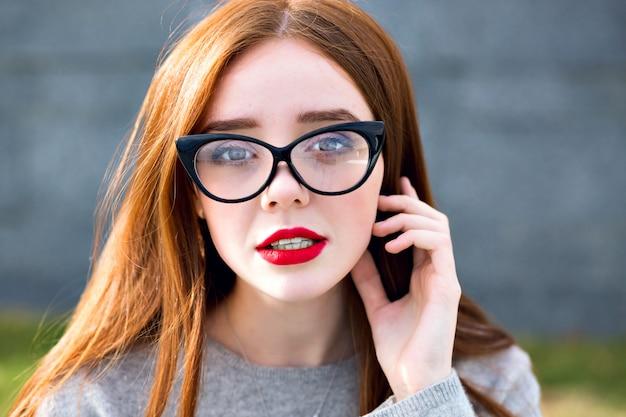 Bliska portret oszałamiającej ślicznej ładnej, ładnej imbirowej nastolatki, jasne okulary przeciwsłoneczne w stylu vintage, styl studencki