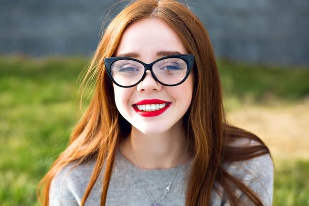 Bliska portret oszałamiającej uroczej ładnej, ładnej rudej nastolatki, niesamowity duży uśmiech, czerwone usta, długie włosy, jasne okulary przeciwsłoneczne w stylu vintage, pozytywny nastrój.