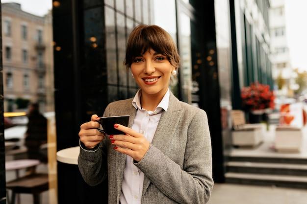 Bliska portret pewnie uśmiechnięta nowoczesna kobieta biznesu z filiżanką kawy na tle dużego budynku biznesowego zdjęcie wysokiej jakości