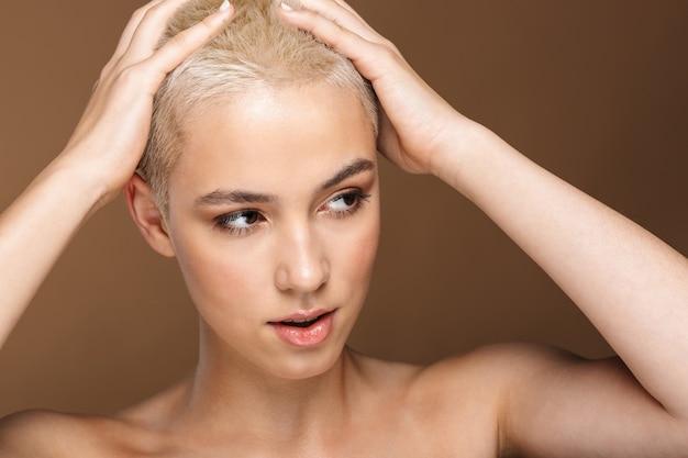 Bliska portret piękna atrakcyjna młoda blondynka z krótkimi włosami pozuje na białym tle na brązowym tle