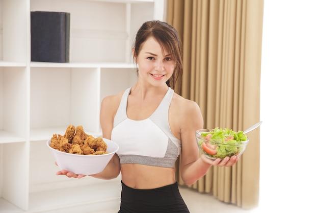 Bliska portret piękna sportowa dziewczyna trzyma miskę smażonego kurczaka i miskę sałatki