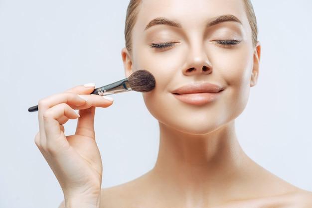 Bliska portret pięknej dziewczyny ma świeżą, zdrową skórę, nakłada kosmetyki na twarz, używa pędzla kosmetycznego