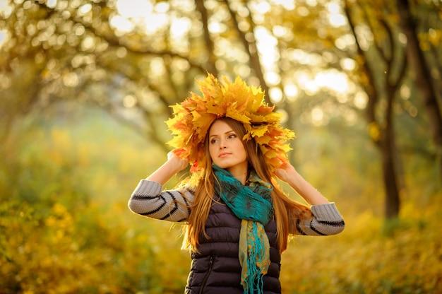 Bliska portret pięknej dziewczyny w ciemnej kamizelce, stoi na tle bajecznej jesieni. bardzo piękna kobieta trzyma na głowie wieniec na wieniec z jesiennymi żółtymi liśćmi.