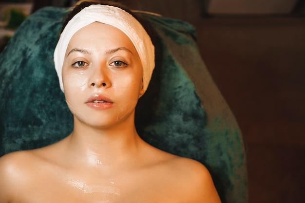 Bliska portret pięknej kobiety rasy kaukaskiej, opierając się na łóżku spa, patrząc na kamery, mając na twarzy maskę przeciw starzeniu się z kwasem hialuronowym.