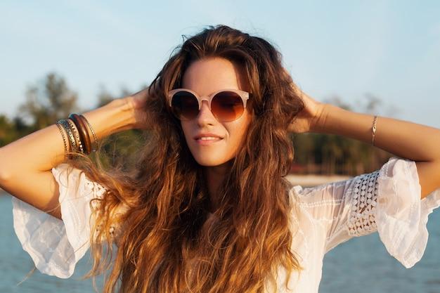 Bliska portret pięknej kobiety w białej sukni na tropikalnej plaży o zachodzie słońca na sobie stylowe okulary przeciwsłoneczne.