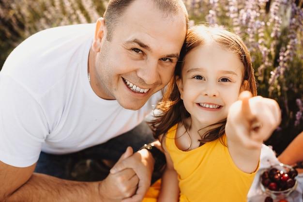 Bliska portret pięknej małej dziewczynki ubranej w żółtą sukienkę, patrząc na kamery, obejmując z ojcem i wskaż aparat w polu z kwiatami.