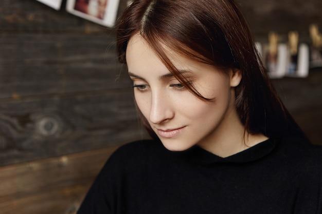 Bliska portret pięknej młodej kobiety europejskiej z czekoladowymi włosami patrząc w dół z nieśmiałym uśmiechem, odpoczywając w przytulnej restauracji podczas lunchu