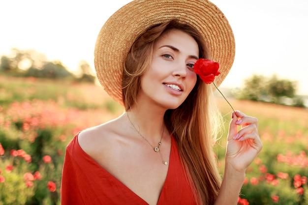 Bliska portret pięknej młodej kobiety romantycznej z kwiatem maku w ręku pozowanie na tle pola. noszenie słomkowego kapelusza. stonowane kolory.