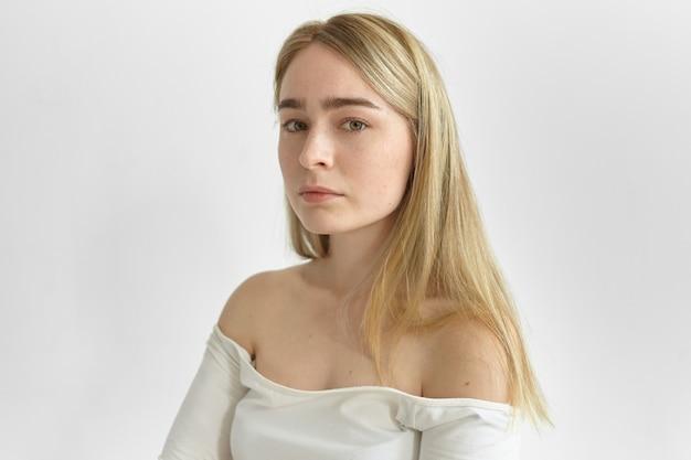 Bliska portret pięknej młodej kobiety z prostymi jasnymi włosami, zielonymi oczami i czystą skórą z piegami, patrząc, pokazując jej nagie ramiona. naturalne piękno, kobiecość, styl i moda