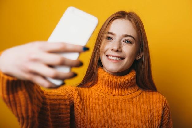 Bliska portret pięknej młodej kobiety z rudymi włosami i piegami robi selfie ze śmiechu smartfona ubrana na żółto na żółtym tle.