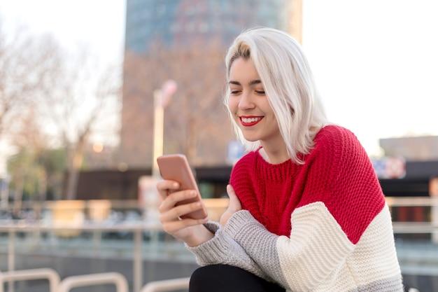 Bliska portret pięknej młodej kobiety za pomocą telefonu komórkowego na zewnątrz w mieście