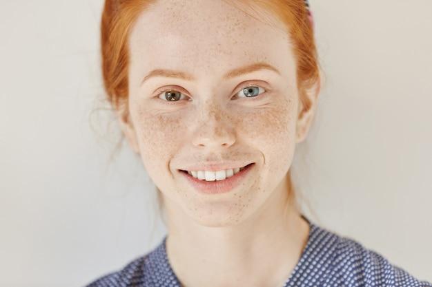 Bliska portret pięknej młodej modelki rudowłosej o różnych kolorach oczu i zdrowej, czystej skórze z piegami, uśmiechając się radośnie, pokazując białe zęby, pozując w pomieszczeniu. heterochromia u człowieka