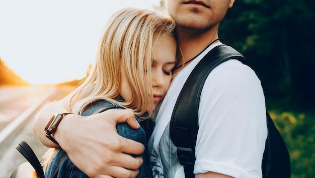 Bliska portret pięknej młodej pary obejmującej, podczas gdy dziewczyna opierając głowę na piersi swojego chłopaka z zamkniętymi oczami przed zachodem słońca podczas podróży.