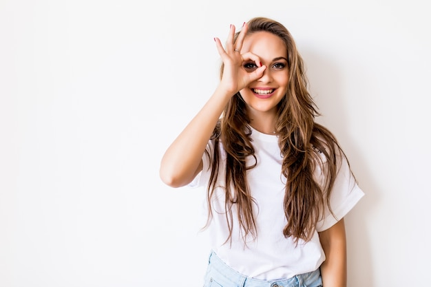 Bliska portret pięknej radosnej blondynki kaukaskiej uśmiechniętej kobiety, demonstrując białe zęby, patrząc w kamerę przez palce w porządku gestu. wyraz twarzy, emocje i język ciała