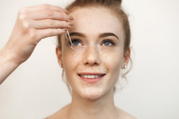 Bliska portret pięknej rudowłosej kobiety nakładającej przezroczystą surowicę z kwasem hialuronowym na jej uśmiechniętą twarz na białym tle.