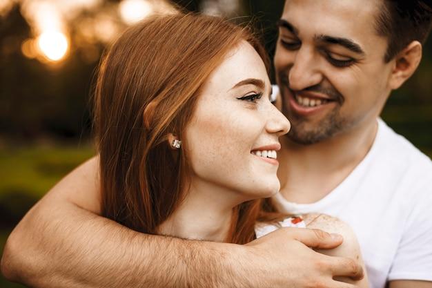 Bliska portret pięknej rudowłosej kobiety z piegami, odwracając się, uśmiechając się, będąc objęty przez jej mężczyznę na zewnątrz przed zachodem słońca podczas randki.