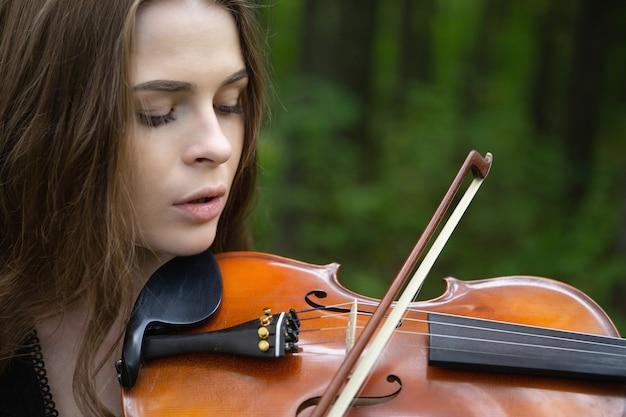 Bliska portret pięknej skrzypaczki kobiety, która ze spuszczonymi oczami