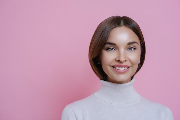 Bliska portret pięknej zadowolonej, radosnej kobiety o ciemnych włosach, uśmiecha się przyjemnie