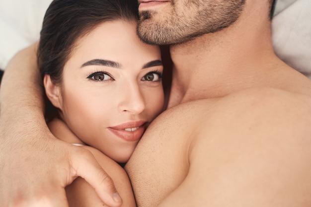 Bliska portret pięknej zadowolonej zrelaksowanej ciemnowłosej młodej kobiety leżącej w objęciach męża