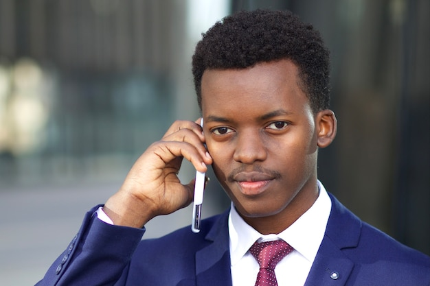 Bliska portret poważnego biznesmena pewność, pracownik biurowy w formalnym garniturze z smartphone. czarny afrykański młody afro amerykanin rozmawia przez telefon komórkowy