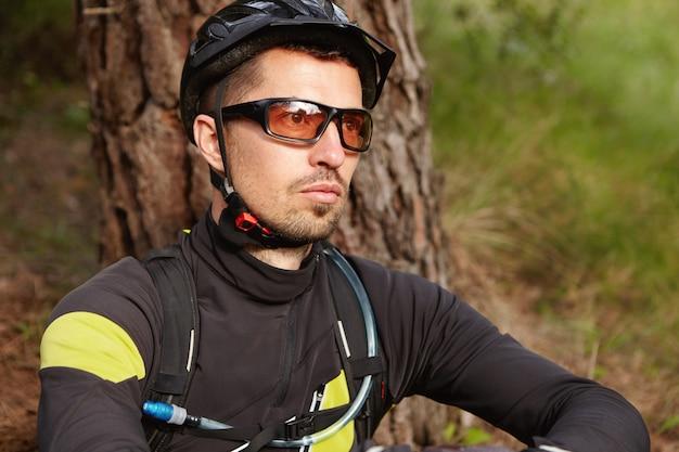 Bliska portret poważnego i przemyślanego jeźdźca z zarostem w odzieży rowerowej, kasku ochronnym i okularach siedzącego na zewnątrz na drzewie i patrzącego przed siebie, myślącego o swoim życiu