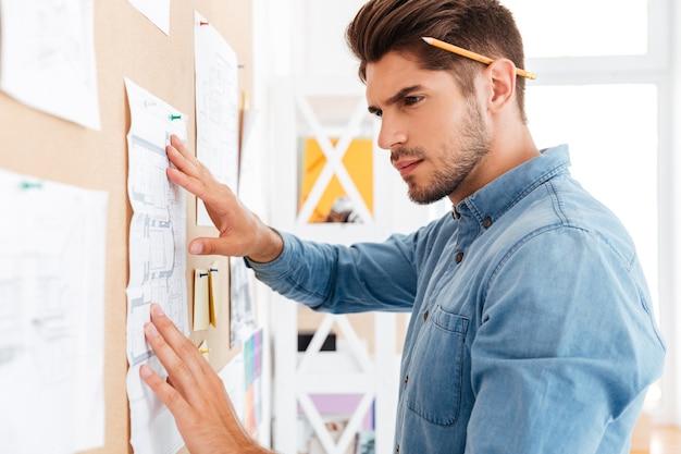 Bliska portret poważnego skoncentrowanego biznesmena publikującego schemat na tablicy w biurze