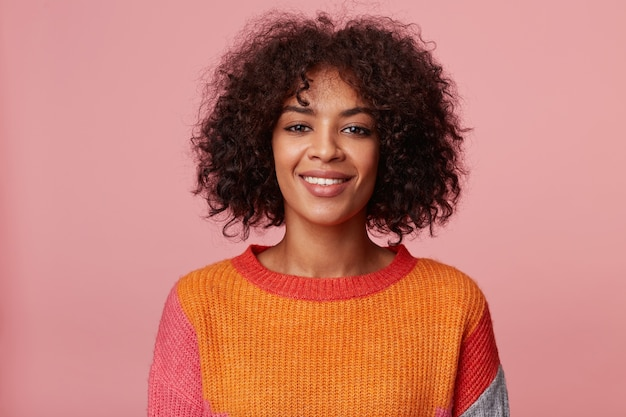 Bliska portret pozytywnej, optymistycznej uroczej afroamerykanki z fryzurą afro wygląda z przyjemnością, z przyjaznym uśmiechem, ubrana w kolorowy longsleeve, na białym tle