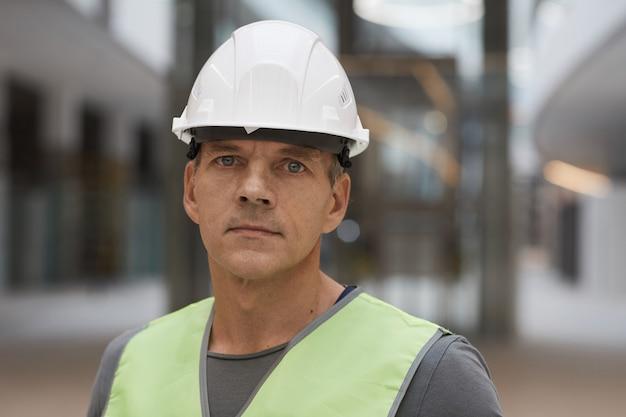 Bliska portret profesjonalnego pracownika budowlanego stojąc na budowie