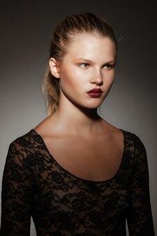 Bliska portret profil piękna blondynka z włosami zebranymi w kucyk, na szarym ciemnym tle.
