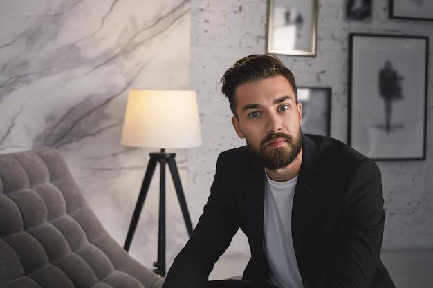 Bliska portret przekonany, atrakcyjny modny młody biznesmen z przyciętą brodą i modną fryzurą pozuje w nowoczesnym, przytulnym wnętrzu, ubrany w formalny stylowy garnitur,