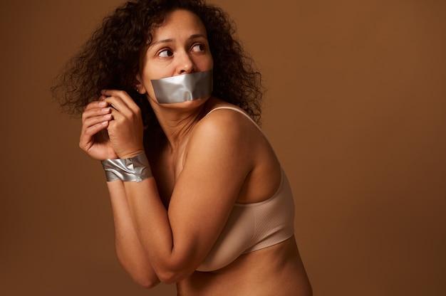 Bliska portret przestraszonej zdesperowanej kobiety z zamkniętymi ustami i związanymi rękami, patrząc wstecz z nadzieją i modląc się o pomoc w zakończeniu przemocy wobec kobiet. koncepcja społeczna, ciemne tło