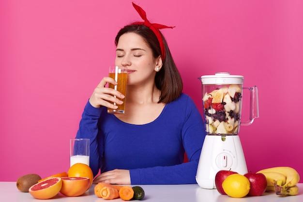 Bliska portret przyjemnej uroczej młodej damy o wąskim owocowym koktajlu z zamkniętymi oczami, cieszy się zapachem, wygląda na szczęśliwego będąc na diecie. pozytywny model siedzi na jasnym różu.