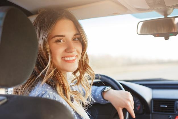 Bliska portret przyjemnie wyglądającej kobiety z radosnym pozytywnym wyrazem, zadowolony z niezapomnianej podróży samochodem, siada na siedzeniu kierowcy, cieszy się muzyką.