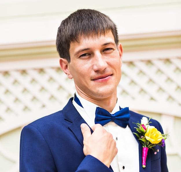 Bliska portret przystojnego stylowego pana młodego w czarnym klasycznym garniturze na zewnątrz