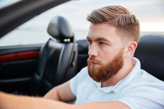 Bliska portret przystojny brodaty mężczyzna jazdy luksusowym samochodem