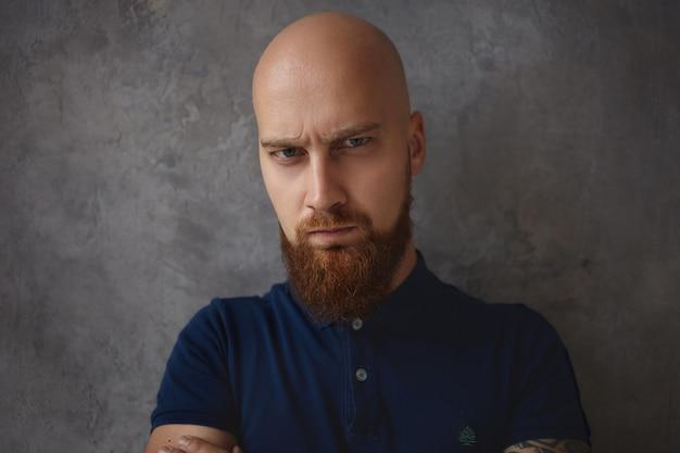Bliska portret przystojny, marszczący brwi, młody łysy mężczyzna z gęstą brodą, mający zrzędliwy, ponury wyraz oczy pełne złości i wściekłości. negatywna mimika i emocje człowieka