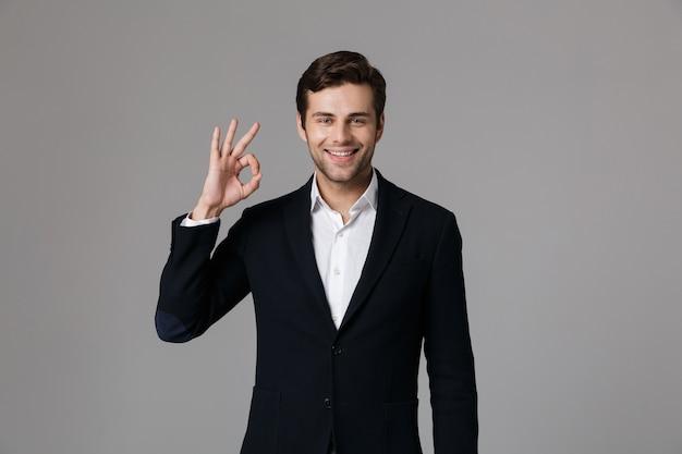 Bliska portret przystojny młody biznesmen ubrany w garnitur na białym tle nad szarą ścianą, pokazując gest ok