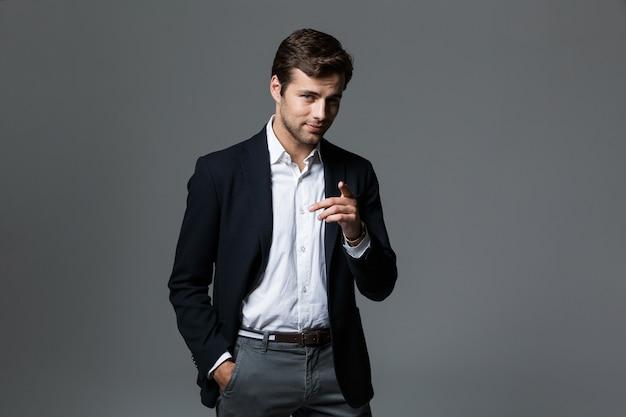 Bliska portret przystojny młody biznesmen ubrany w garnitur na białym tle nad szarą ścianą, wskazując palcem