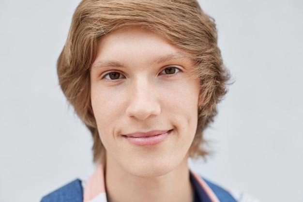 Bliska portret przystojny młody chłopak ze stylową fryzurę, ciemne wąskie oczy, cienkie usta, czystą zdrową skórę