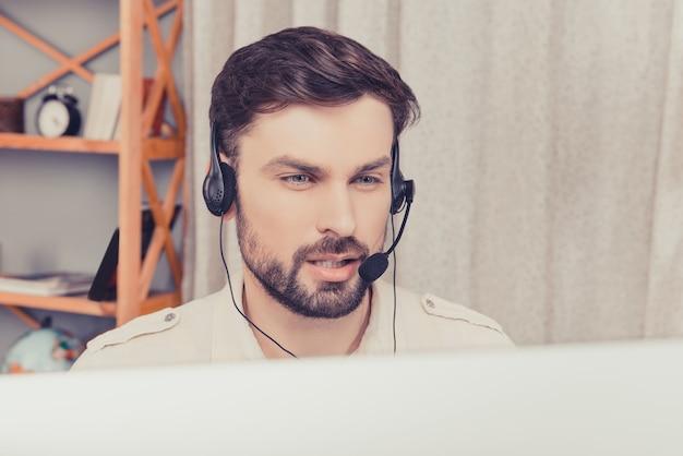 Bliska portret przystojny młody pracownik w słuchawkach
