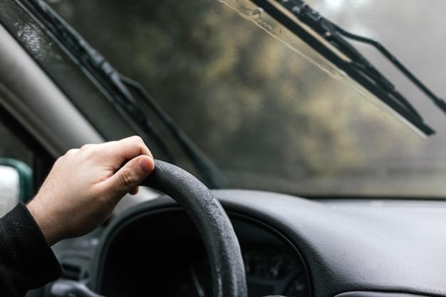 Bliska portret ręki nierozpoznawalnego mężczyzny prowadzącego kierownicę samochodu podczas podróży w mglisty i deszczowy zimowy dzień
