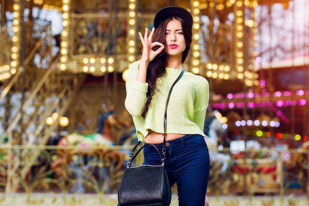 Bliska portret sexy fantazyjne stylowe kobiety zabawy i uśmiech na atrakcje. nosi modny hipsterski swag czarny kapelusz i neonowy sweter.
