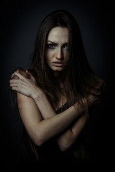 Bliska portret smutnej kobiety ze skrzyżowanymi rękami